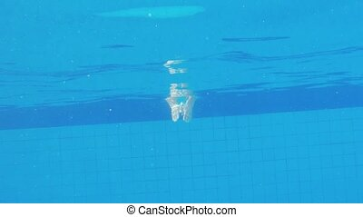 Young brunette woman jumping underwater in the swimming pool...