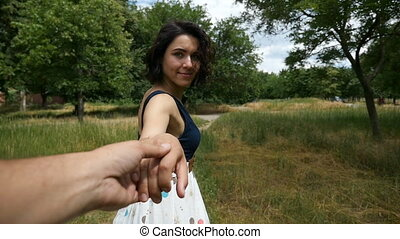 Young brunette woman keeps a hand of some man and runs forward in slow motio