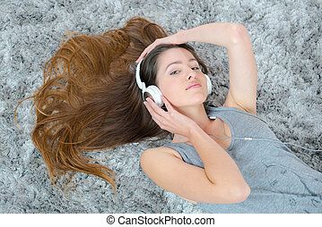 young brunette woman listening music while laying on the carpet