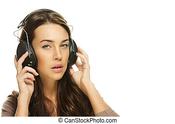 young brunette woman listening to music on white background