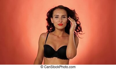 Young, brunette woman looking at camera in sexual black bra on vinous background, slow motion