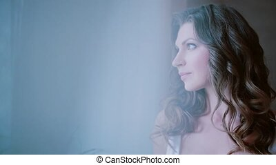 Young brunette woman looking at window in the morning. Beautiful girl doing up hair. View through the curtain.