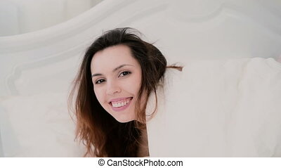 Young brunette woman lying on the bed and playing with hair in light apartment. Girl looks at camera and cute smile.