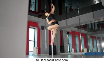 Young brunette woman performing pole dance in a studio