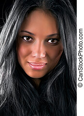 Young brunette woman portrait. On dark background.