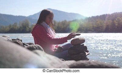 Young brunette woman putting pebble stack next to the...