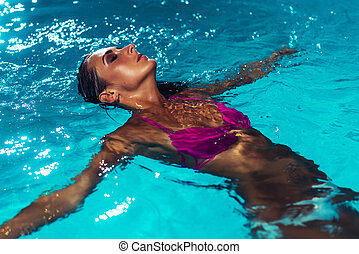 Young brunette woman relaxing in the swimming pool.