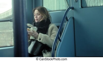 young brunette woman rides on public transport, uses the...