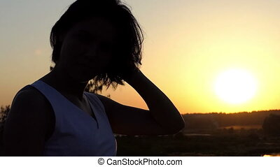 Young Brunette Woman Sets Her Hair up on a Lake Bank at Sunset in Slow Motion