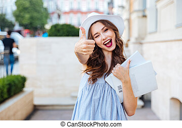 Young brunette woman showing thumbs up