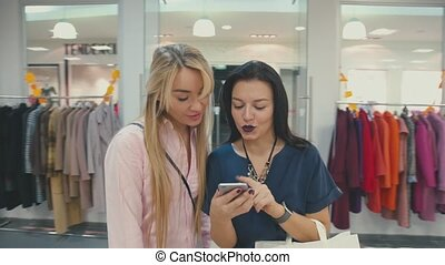 Young brunette woman shows her friend image on smartphone. Shopping