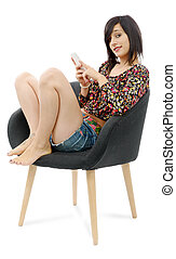 young brunette woman sitting in a armchair with a phone