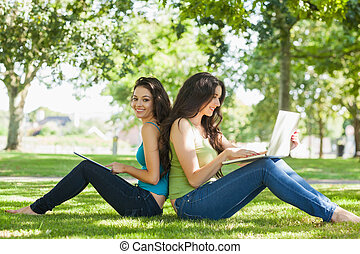 Young brunette woman sitting with her friend on a lawn