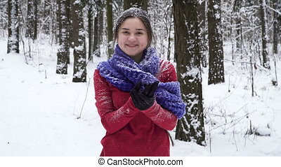 Young brunette woman sprinkled with snow in winter forest is...