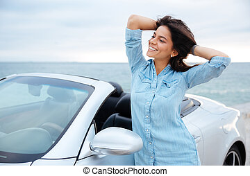 Young brunette woman standing next to her new car