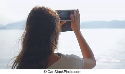 Young brunette woman standing on deck of cruise ship and takes photo with smart phone in slow motion. 1920x1080, hd