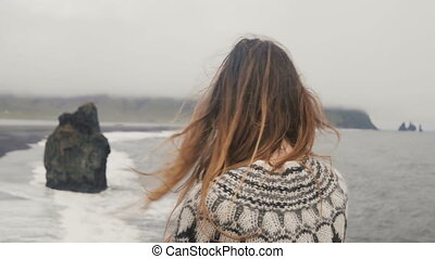 Young brunette woman standing on the shore of the sea and...