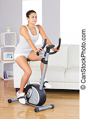 Young brunette woman training on an exercise bike