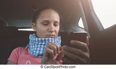 Young brunette woman uses mobile phone in the car while traveling.