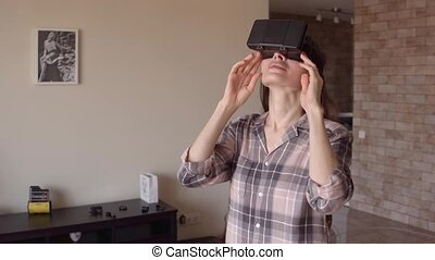 Young brunette woman using her phone VR headset at home. Virtual reality glasses in action. 4K steadicam video