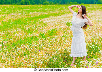 young brunette woman walking in a field with daisies