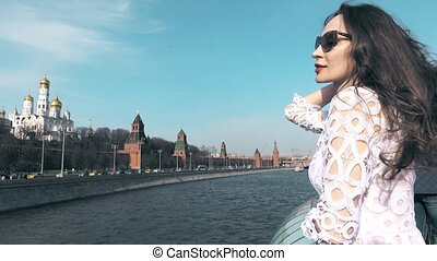 Young brunette woman watching at Moscow Kremlin. Travel to Russia concept. 4K video
