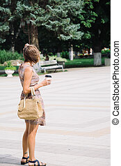 Young brunette woman with coffee cup walking in city