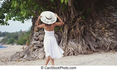 Young brunette woman with long hair in white drees and hat beckons to follow her throws the hat on tropical beach. slow motion.