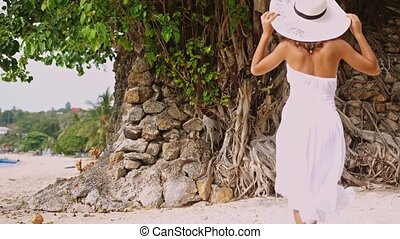 Young brunette woman with long hair in white drees and hat...