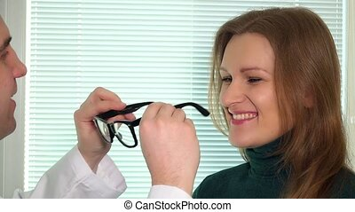 young brunette woman with optician doctor man trying eyeglasses