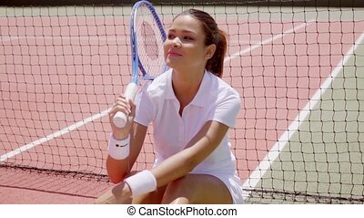 Young Brunette Woman with Racket Sitting on Court