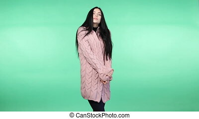 woman wrapping up in a pink cardigan - Young brunette woman...