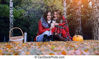 Young brunette women sitting on picnic bundled up in a blanket drinking hot tea from thermos in autumn park. Girls rug near the pumpkin of Halloween theme