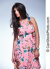 woman in pink floral dress is looking to her side