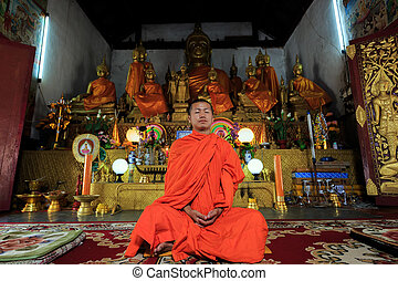 Young Buddhist Monk meditating - A monk meditating in the...
