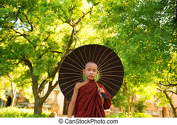 Young Buddhist monk walking outdoors under shade of green tree with umbrella, outside monastery, Myanmar.