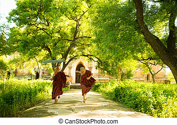 Young Buddhist novice monks running outside monastery