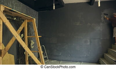 Young builder accurately paints wall with gray suffusion in art studio.