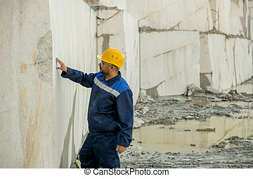 Young builder in workwear touching wall surrounding quarry