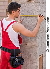 Young builder measuring wall