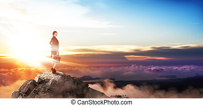Young buiness woman stands on the top of the mountain.