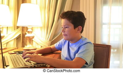 Young burunette boy using laptop