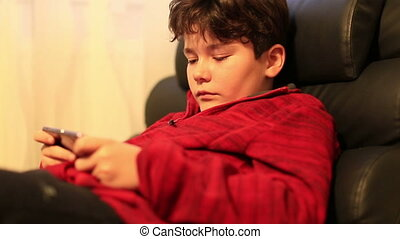 Young burunette child with smart phone at home