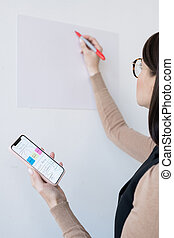 Young business coach holding smartphone with flow chart before presentation