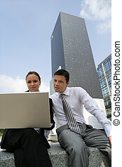 Young business couple sat with laptop in city centre