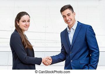 Young business couple shaking hands.