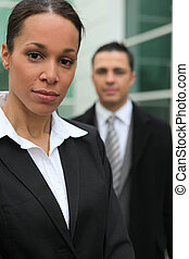 Young business couple stood in front of their office