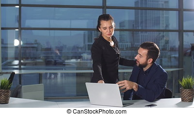 Young business couple talking and using tablet in office
