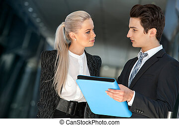 Young business couple talking with file.