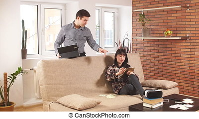 Young business couple using laptop at home.